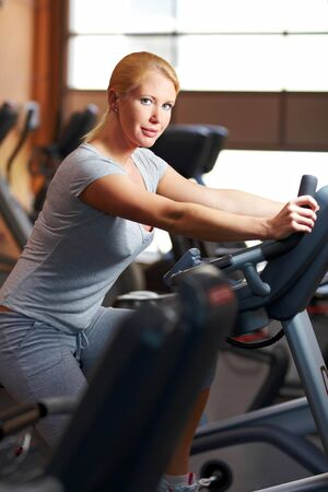 home trainer: Woman in a gym using a home trainer