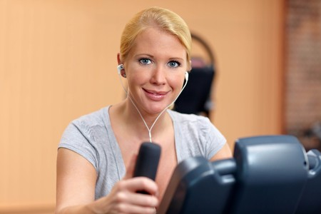 hometrainer: Happy woman in gym on a hometrainer listening to music