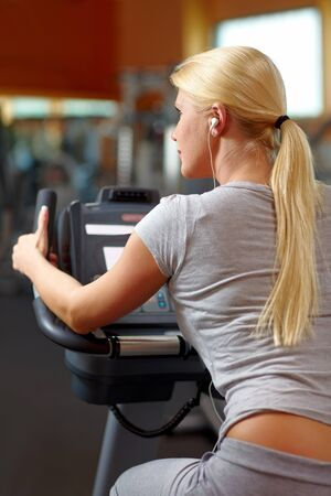 Happy woman in gym on a hometrainer listening to music Stock Photo - 7940565