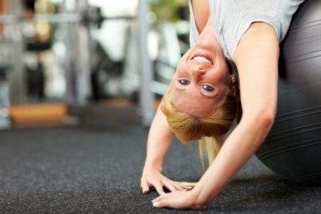 Happy woman in a gym exercising with a gym ball Stock Photo - 7940557