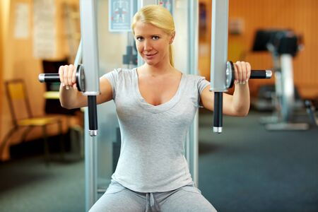 Happy woman in a gym exercising her muscles Stock Photo - 7940556