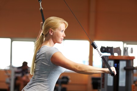 Happy woman training on a machine in a gym photo