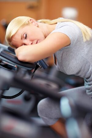 hometrainer: Sleeping woman in gym with her head on a hometrainer