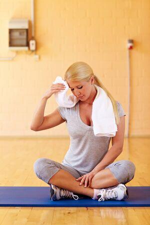 sudando: Mujer tomando un descanso en el gimnasio de la sudoración  Foto de archivo