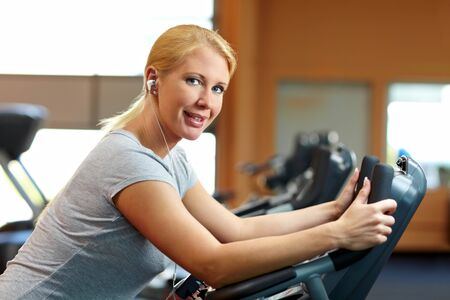 Happy woman in gym on a hometrainer listening to music Stock Photo - 7940574