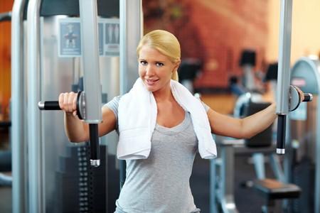training device: Female hand holding handle on training machine in gym