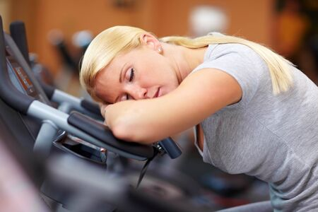 Sleeping woman in gym with her head on a hometrainer Stock Photo - 7940575
