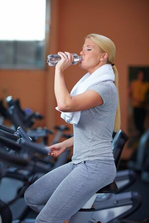 Thirsty woman drinking water in a gym Stock Photo - 7940577