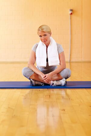 Happy woman in gym sitting in tailor seat photo