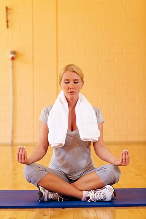 Relaxed woman sitting in tailor seat in gym and meditating photo