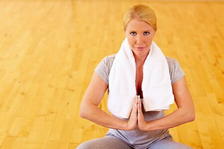 tailor seat: Relaxed woman sitting in tailor seat in gym and meditating Stock Photo
