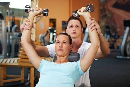 Woman doing Gewichttraining mit dem Fitness coach Standard-Bild