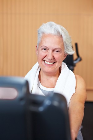 Happy smiling senior woman exercising in a gym Stock Photo - 8128583