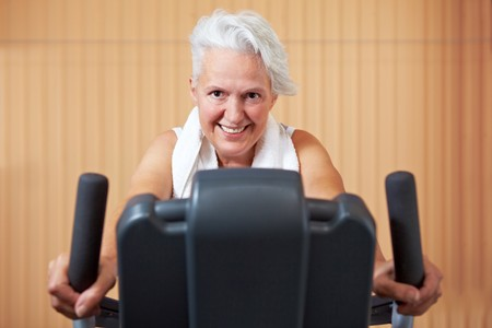 Elderly woman exercising on bicycle in a gym photo
