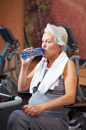 hometrainer: Senior woman drinking water in a gym Stock Photo