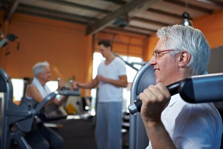 Two senior people working out in a gym with fitness coach photo