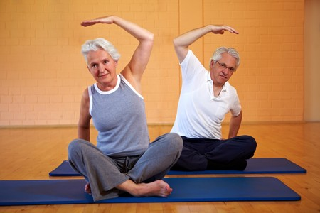 Two senior people doing gymnastics in a gym photo