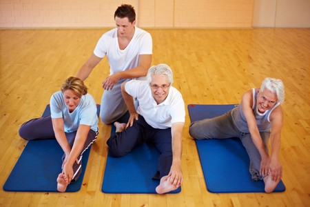 senior yoga: Fitness trainer showing stretching exercises to a group Stock Photo