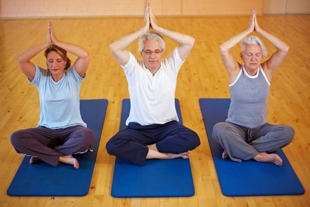 Three people doing Yoga in a gym photo