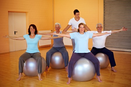 rehab: Fitness group in gym doing back exercises Stock Photo