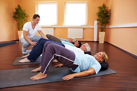 pilates man: Group doing back exercises in a gym Stock Photo