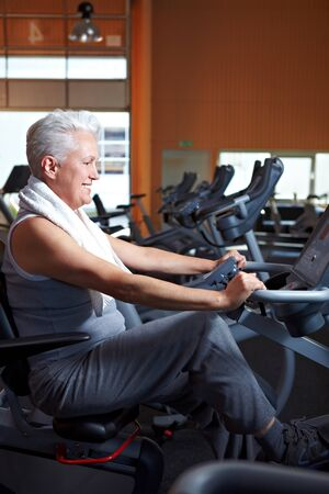 Elderly woman exercising on bicycle in a gym Stock Photo - 8128553