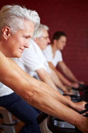 Senior woman on spinning bike in a gym photo