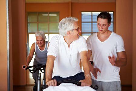 Fitness coach explaining spinning exercises to two senior people photo