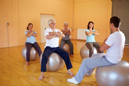 Group in gym doing fitness exercises on exercise ball photo
