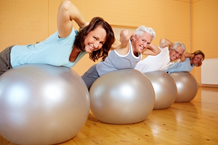 Group in gym doing back exercises on Swiss balls photo