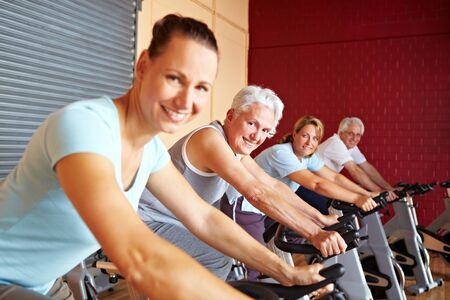 Mensen in een sportschool zittend op spin bikes Stockfoto