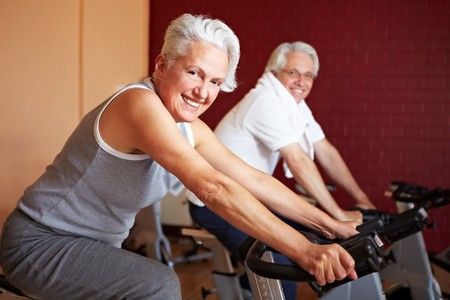 hometrainer: Two happy senior people on spinning bikes in gym