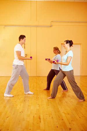 Dos mujeres haciendo ejercicios de pesas con entrenador personal en gimnasio  Foto de archivo - 8128505