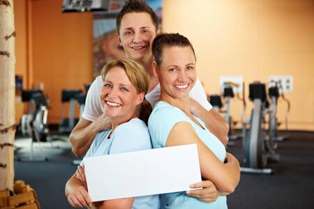 Two women and a man holding an empty sign in a gym Stock Photo