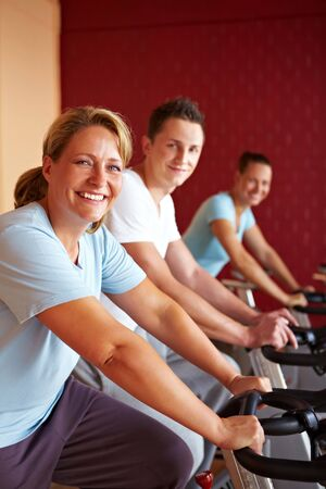 overweight people: Three people working out on spinning bikes in gym