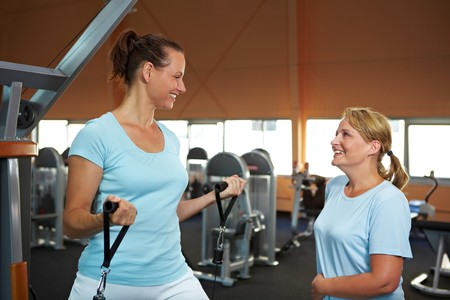 Two sportive women in gym talking to each other photo