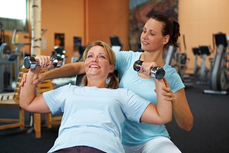 personal trainer: Woman doing weight training with female fitness coach