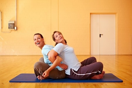 Two happy Best Ager doing back exercises in gym photo