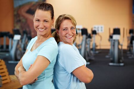 Two happy sporty women standing in a gym photo