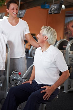 Eldery man doing back exercises in gym with fitness coach photo