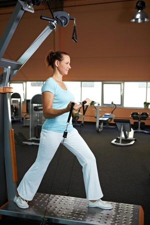 training device: Woman doing weight training in a gym Stock Photo