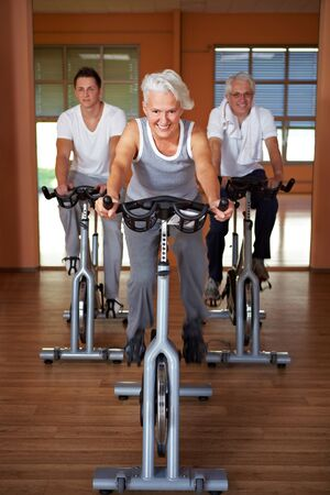 wheel spin: Spinning class with senior people in a gym Stock Photo
