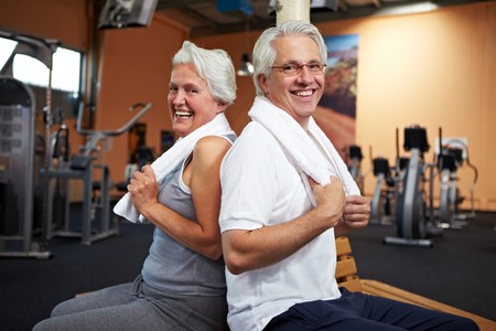 fitness couple: Happy senior couple with towels in a gym