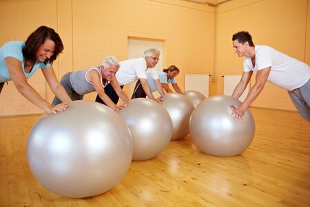 Group in gym doing pushups on exercise ball photo