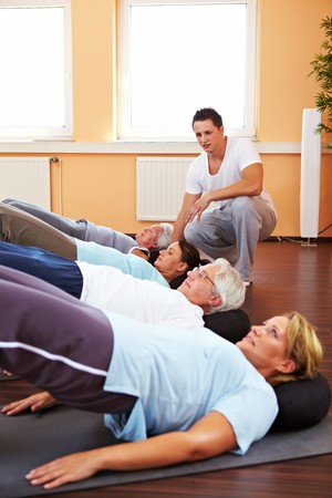 senior citizens: Group doing back exercises in a gym with fitness trainer