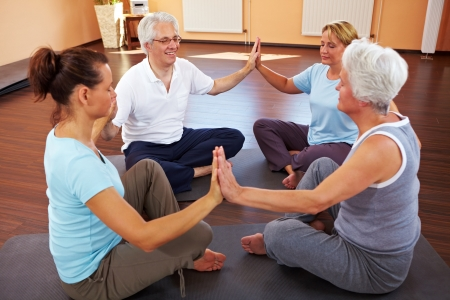 meditating woman: Happy group meditating in circle in a gym Stock Photo