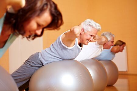 Group in gym doing back exercises on Swiss balls Stock Photo - 8128519