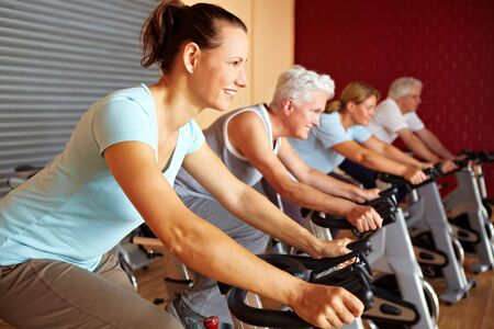 hometrainer: People in a gym sitting on spinning bikes Stock Photo
