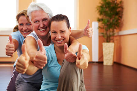 Three happy women in a gym holding their thumbs up Stock Photo - 8128473