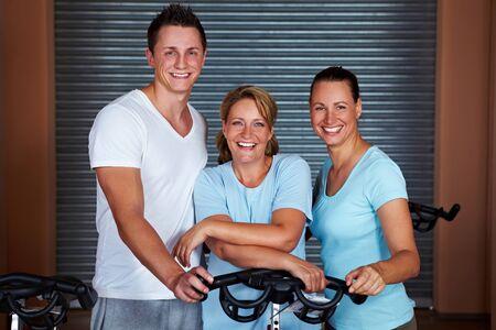Three happy people standing around spinning bikes in gym photo